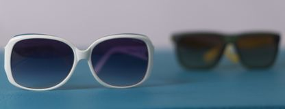 two side-by-side sunglasses modern and actual glasses royalty free stock images
