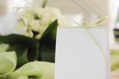 Placeholder z zielonym faborkiem na stole z bukietem biel Obrazy Royalty Free