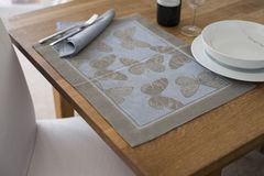 Placemat with Butterfly Design on Table with Bowl and Utensils Royalty Free Stock Photography
