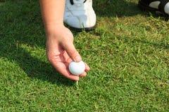 Placement de la bille de golf sur un té photographie stock