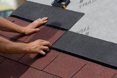 Placement of tiles. Placement of asphalt shingles on a roof of wood Stock Image