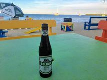Placencia, Belize - May 26th, 2018: A cool tasty bottle of Belikin beer resting on a table along the beautiful sandy beaches of P stock image