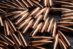 Placer copper bullets on a dark wooden background Stock Images