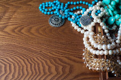 Placer jewelry and ornaments on the wooden table Royalty Free Stock Photo