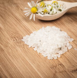 Placer sea salt, chamomile flowers on a wooden spoon Stock Images