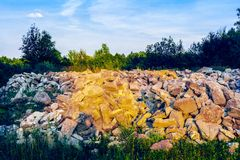 Placer of stone boulders among grass and trees Royalty Free Stock Images