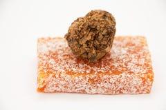 Placer turco anaranjado con el caramelo de chocolate en un fondo gris Imagen de archivo