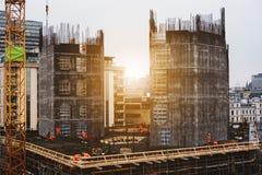 Placera konstruktion i staden med arbetare som arbetar i soluppgång Arkivfoto