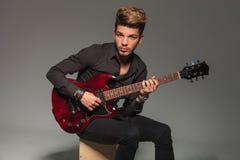 Placerad ung man som spelar en elektrisk gitarr royaltyfria foton