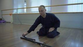 Placerat på golvsamurajerna gör en pilbåge till golvet av det Catana svärdet, stiger därefter honom stock video