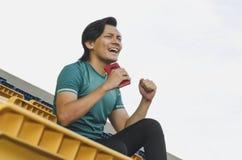 Placering för ung man och rymma handtelefonen över vit bakgrund arkivfoton