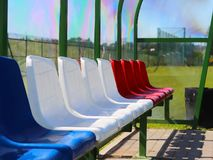 Places for coaches and reserve players on the football field. Plastic colored benches under a canopy of transparent fiberglass. Re. D, blue and white colors Stock Photo
