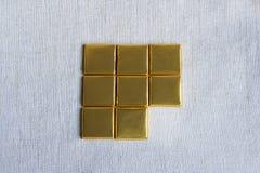 Places d'or enveloppées de barre de chocolat Photographie stock libre de droits