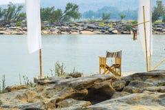 Placesd da cadeira em um cais do rio Imagens de Stock