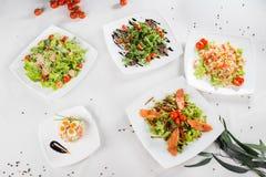 Placez avec différentes salades sur le fond blanc images libres de droits