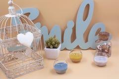 Placez de la décoration intérieure avec plusieurs différents objets, cage, bougies d'usines et lettres images stock