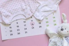 Placez des accessoires nouveau-nés en prévision de l'enfant - calendrier avec le numéro cerclé 18 dix-huit, les vêtements de bébé photos stock