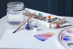 Placez des aquarelles, des brosses, d'un verre de l'eau et d'une palette sur une feuille blanche, belles courses d'aquarelle photo libre de droits