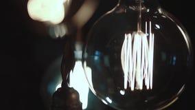 Placez des belles petites lampes à lueur dans une chambre noire, les lampes balancent banque de vidéos