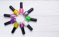 Placez des bouteilles de vernis ? ongles dans la couleur diff?rente sur le fond en bois blanc image libre de droits
