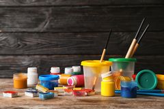 Placez des matériaux de peinture d'enfant sur la table près du mur en bois photo stock