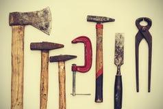 Placez des outils de construction de main de cru sur un fond en bois blanc, rétro concept photos stock