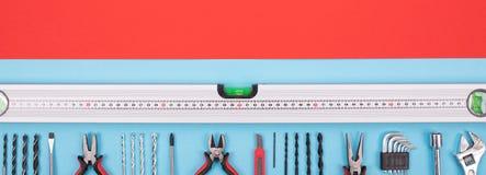 Placez des outils de construction sur le fond rouge-bleu images stock