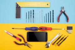 Placez des outils de métal ouvré avec le smartphone sur le fond coloré photo libre de droits