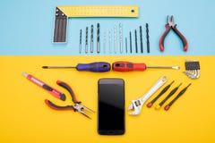 Placez des outils de métal ouvré avec le smartphone sur le fond coloré photos libres de droits