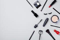 Placez des produits de beauté et les outils de maquillage ont décoré des confettis d'étoile sur la vue supérieure grise de table  photographie stock libre de droits