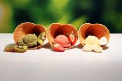 Placez des scoops de crème glacée de différentes couleurs et saveurs avec des baies et des fruits images libres de droits