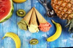 Placez des scoops de crème glacée de différentes couleurs et saveurs avec des baies et des fruits photos stock