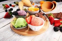 Placez des scoops de crème glacée de différentes couleurs et saveurs avec les baies, le chocolat et les fruits photographie stock libre de droits