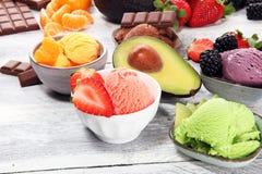 Placez des scoops de crème glacée de différentes couleurs et saveurs avec les baies, le chocolat et les fruits images libres de droits