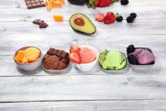 Placez des scoops de crème glacée de différentes couleurs et saveurs avec les baies, le chocolat et les fruits images stock