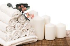 Placez des serviettes blanches de petit pain avec des fleurs et des bougies d'isolement sur le blanc photos libres de droits