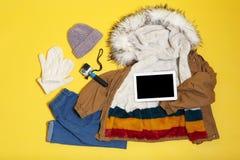 Placez des vêtements et des dispositifs chauds sur le fond de couleur, configuration plate image libre de droits