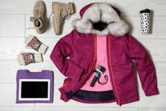 Placez des vêtements et des dispositifs chauds sur le fond en bois, configuration plate images stock