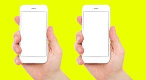 Placez deux téléphones différents avec l'affichage neutre sur le fond jaune, les mains masculines tiennent des téléphones photo libre de droits