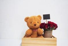Placez l'ours et les roses de nounours de cadeau avec la table des messages avec l'espace pour Photographie stock