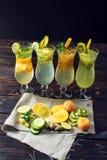 Placez la limonade avec de la glace dans l'ouragan en verre avec les fruits tropicaux Photographie stock