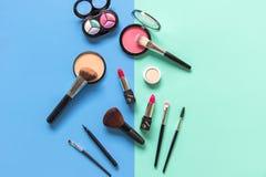 Placez le maquillage de cosmétiques, la brosse, le fard à paupières et le rouge à lèvres, le fond bleu et vert coloré Photo stock