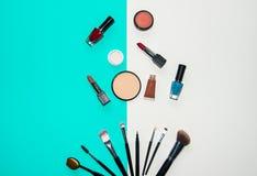 Placez le maquillage de cosmétiques, la brosse, le fard à paupières et le rouge à lèvres, fond coloré Photo stock