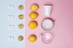 placez le thé Sucre raffiné, citron, orange, tasses et cuillères comme ornement sur un papier rose et bleu image libre de droits