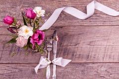 Placez les arrangements de table avec la fourchette et le couteau, attachés avec un ruban blanc de satin, et les fleurs sur une v Photographie stock