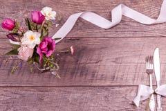 Placez les arrangements de table avec la fourchette et le couteau, attachés avec un ruban blanc de satin, et les fleurs sur une v Image stock