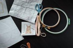placez les ciseaux de soie de broderie filètent pour broder sur la table foncée Photo stock