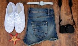 Placez les vêtements pour aller à la mer : les jeans court-circuite, des espadrilles, montres, photocamera, les coquilles, une vu Images libres de droits