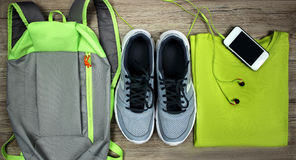 Placez pour des chaussures de sports, sac à dos, le T-shirt, téléphone portable avec des écouteurs en gros plan sur un fond en bo Photos libres de droits