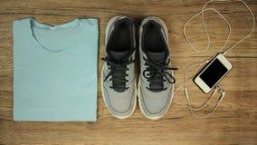 Placez pour des sports : chaussures, T-shirt, téléphone portable avec des écouteurs en gros plan sur un fond en bois, vue supérie Photo stock